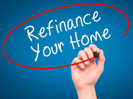 refinance: Man Hand writing Refinance Your Home with black marker on visual screen. Isolated on blue. Business, technology, internet concept. Stock Image Stock Photo