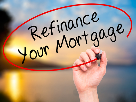 refinance: Man Hand writing Refinance Your Mortgage with black marker on visual screen. Isolated on nature. Business, technology, internet concept. Stock Image
