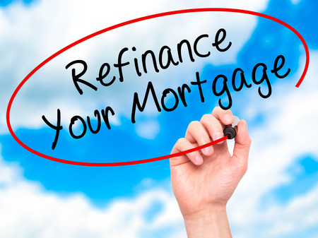 loaning: Man Hand writing Refinance Your Mortgage with black marker on visual screen. Isolated on sky. Business, technology, internet concept. Stock Image
