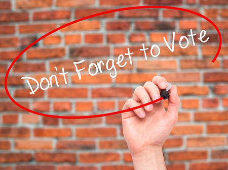 governing: Man Hand writing Dont Forget to Vote with black marker on visual screen. Isolated on bricks. Business, technology, internet concept. Stock Photo Stock Photo