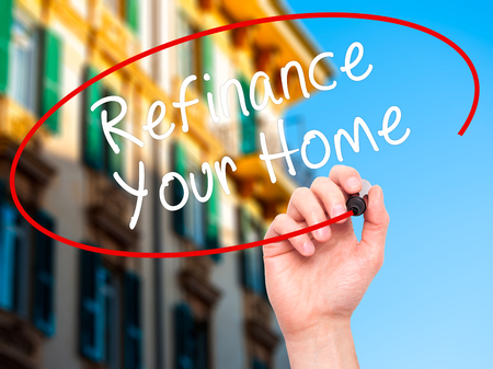 Man Hand writing Refinance Your Home with black marker on visual screen. Isolated on buildings. Business, technology, internet concept. Stock Image Stock Photo