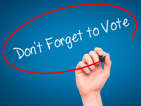 governing: Man Hand writing Dont Forget to Vote with black marker on visual screen. Isolated on blue. Business, technology, internet concept. Stock Photo
