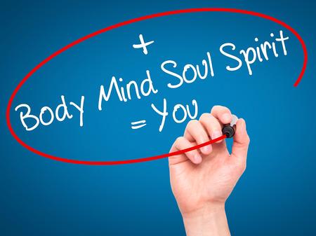 Man Main écrire Body + Esprit + âme + Esprit = Vous avec un marqueur noir sur l'écran visuel. Isolé sur le bleu. La vie, la technologie, internet concept. image