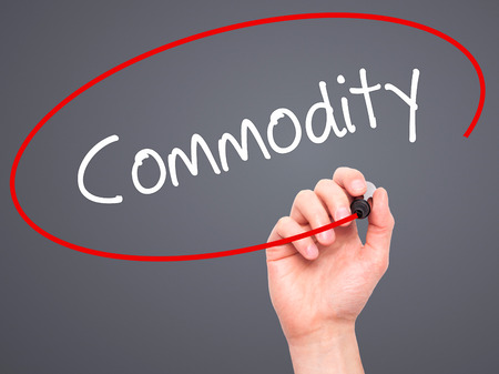commodity: Man Hand writing Commodity with black marker on visual screen. Isolated on grey. Business, technology, internet concept. Stock Photo