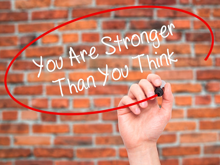 stronger: Man Hand writing You Are Stronger Than You Think with black marker on visual screen. Isolated on bricks. Business, technology, internet concept. Stock Photo Stock Photo