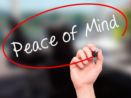 sense of security: Man Hand writing Peace of Mind black marker on visual screen. Isolated on office. Business, technology, internet concept. Stock Image