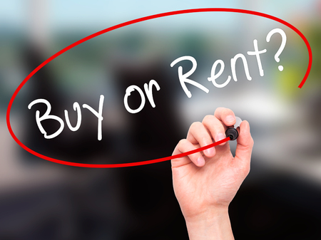 buying questions: Man Hand writing Buy or Rent? with black marker on visual screen. Isolated on office. Business, technology, internet concept. Stock Image Stock Photo