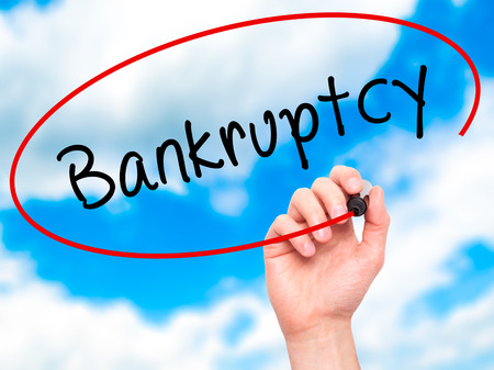 creditors: Man Hand writing Bankruptcy with black marker on visual screen. Isolated on sky. Business, technology, internet concept. Stock Image
