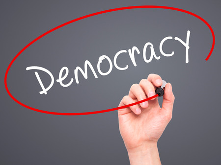 presidency: Man Hand writing Democracy with black marker on visual screen. Isolated on grey. Business, technology, internet concept. Stock Image