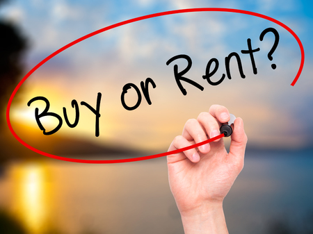 buying questions: Man Hand writing Buy or Rent? with black marker on visual screen. Isolated on naturel. Business, technology, internet concept. Stock Image