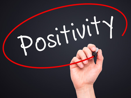 street wise: Man Hand writing Positivity with black marker on visual screen. Isolated on black. Business, technology, internet concept. Stock Image