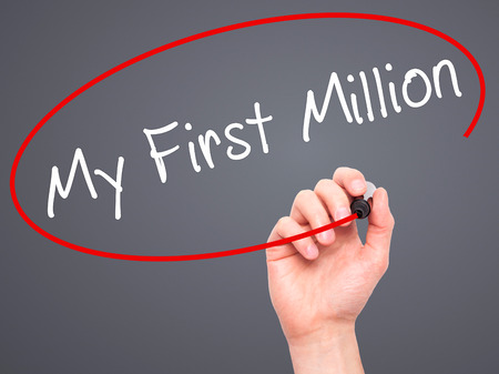 Man Hand writing My First Million with black marker on visual screen. Isolated on grey. Business, technology, internet concept. Stock Image