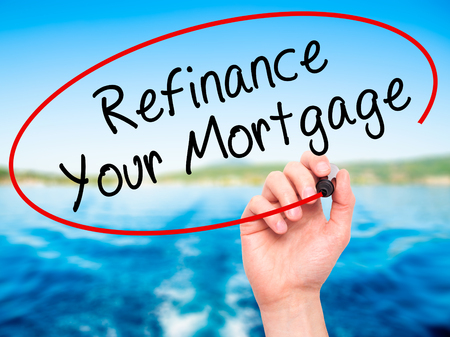 refinancing interest rates: Man Hand writing Refinance Your Mortgage with black marker on visual screen. Isolated on nature. Business, technology, internet concept. Stock Image