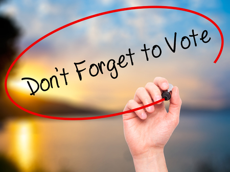 governing: Man Hand writing Dont Forget to Vote with black marker on visual screen. Isolated on sky. Business, technology, internet concept. Stock Photo