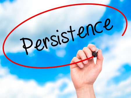 persistence: Man Hand writing Persistence  with black marker on visual screen. Isolated on sky. Business, technology, internet concept. Stock Photo Stock Photo