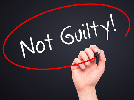 white backing: Man Hand writing NOT GUILTY with black marker on visual screen. Isolated on black. Business, technology, internet concept. Stock Image Stock Photo