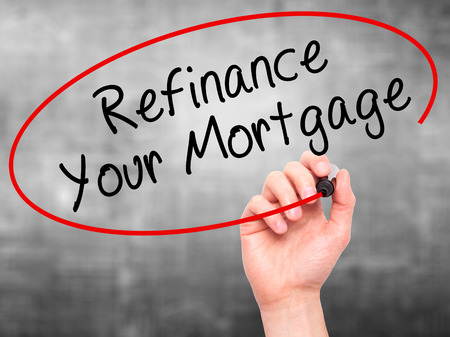refinancing interest rates: Man Hand writing Refinance Your Mortgage with black marker on visual screen. Isolated on grey. Business, technology, internet concept. Stock Image