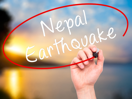 quake: Man Hand writing Nepal Earthquake with black marker on visual screen. Isolated on nature. Business, technology, internet concept. Stock Image