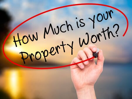 Man Hand writing How Much is your Property Worth? with black marker on visual screen. Isolated on nature. Business, technology, internet concept. Stock Image Stock fotó
