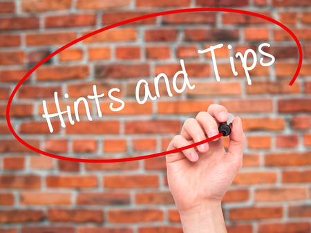 hints: Man Hand writing Hints and Tips with black marker on visual screen. Isolated on bricks. Business, technology, internet concept. Stock Photo