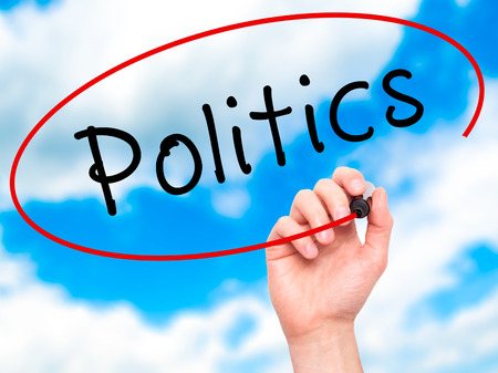 nomination: Man Hand writing Politics with black marker on visual screen. Isolated on sky. Business, technology, internet concept. Stock Image Stock Photo