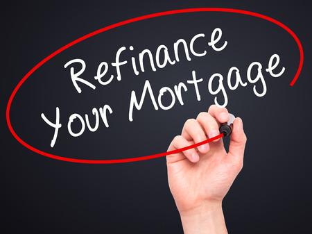Man Hand schriftlich refinanzieren Ihre Hypothek mit schwarzen Marker auf visuellen Bildschirm. Isoliert auf schwarz. Wirtschaft, Technik, Internet-Konzept. stock Image Standard-Bild