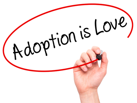 mother in law: Man Hand writing Adoption is Love with black marker on visual screen. Isolated on white. Adoption, technology, internet concept. Stock Photo