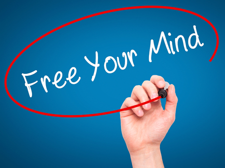 free your mind: Man Hand writing Free Your Mind with black marker on visual screen. Isolated on blue. Business technology, internet concept. Stock Image Stock Photo