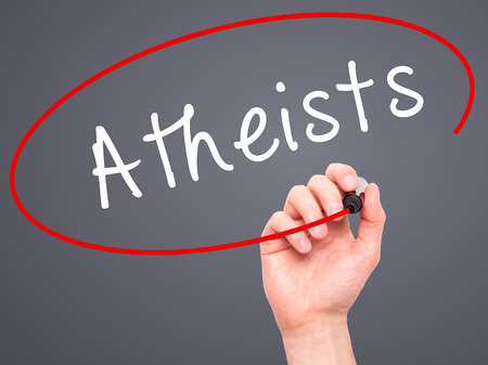nonbelief: Man Hand writing Atheists with black marker on visual screen. Isolated on grey. Business, technology, internet concept. Stock Image