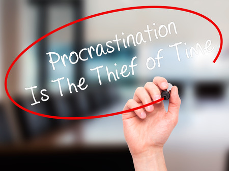 procrastination: Man Hand writing  Procrastination Is The Thief of Time with black marker on visual screen. Isolated on office. Business, technology, internet concept. Stock Image