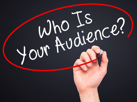 validated: Man Hand writing Who Is Your Audience? with black marker on visual screen. Isolated on black. Business, technology, internet concept. Stock Image