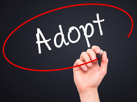 adopting: Man Hand writing Adopt  with black marker on visual screen. Isolated on black. Business, technology, internet concept. Stock Photo Stock Photo