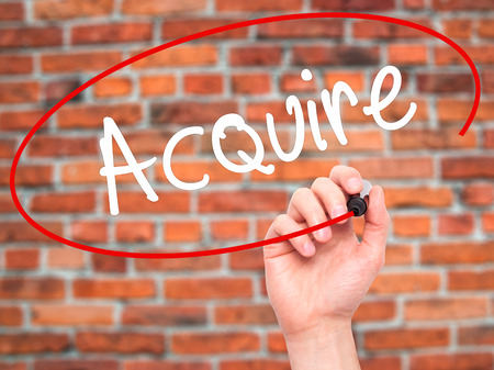 acquire: Man Hand writing Acquire with black marker on visual screen. Isolated on background. Business, technology, internet concept. Stock Photo