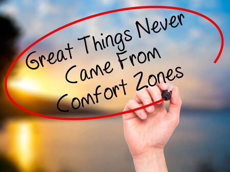 came: Man Hand writing Great Things Never Came From Comfort Zones with black marker on visual screen. Isolated on nature. Business, technology, internet concept. Stock Image