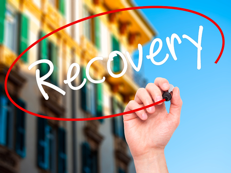 recovery position: Man Hand writing  Recovery  with black marker on visual screen. Isolated on city. Life, technology, internet concept. Stock Image