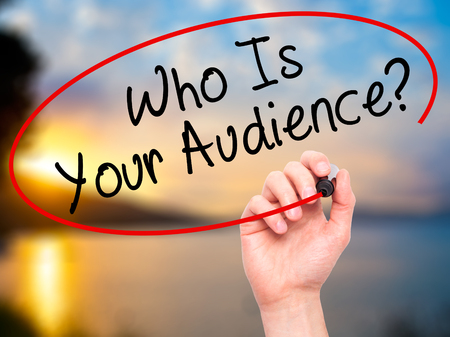 qualify: Man Hand writing Who Is Your Audience? with black marker on visual screen. Isolated on nature. Business, technology, internet concept. Stock Image