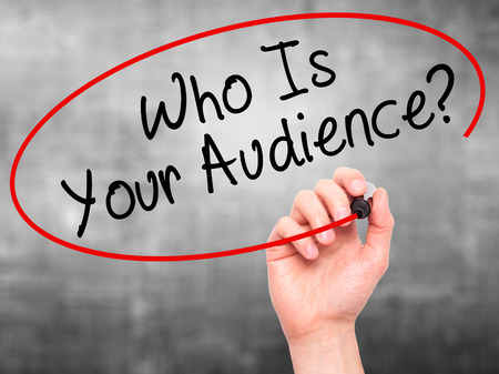 validated: Man Hand writing Who Is Your Audience? with black marker on visual screen. Isolated on grey. Business, technology, internet concept. Stock Image