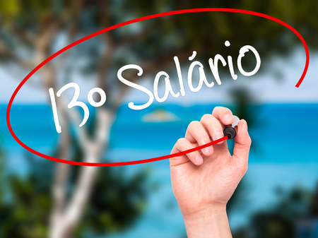 monetizing: Man Hand writing 13 Salary (13o salario In Portuguese)  with black marker on visual screen. Isolated on background. Business, technology, internet concept. Stock Photo