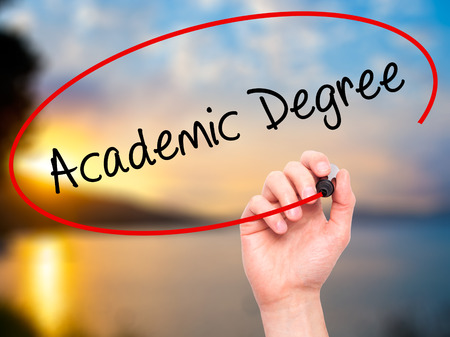 business degree: Man Hand writing Academic Degree with black marker on visual screen. Isolated on nature. Business, technology, internet concept. Stock Photo Stock Photo