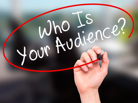 validated: Man Hand writing Who Is Your Audience? with black marker on visual screen. Isolated on office. Business, technology, internet concept. Stock Image