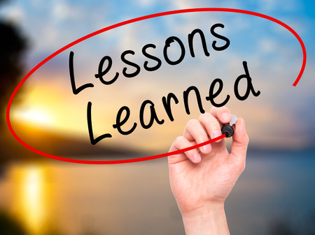 learned: Man Hand writing Lessons Learned with black marker on visual screen. Isolated on nature. Business, technology, internet concept. Stock Image