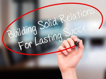 lasting: Man Hand writing Building Solid Relations For Lasting Success with black marker on visual screen. Isolated on office. Business, technology, internet concept. Stock Image Stock Photo