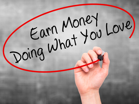 earn money: Man Hand writing Earn Money Doing What You Love with black marker on visual screen. Isolated on grey. Health, technology, internet concept. Stock Image Stock Photo