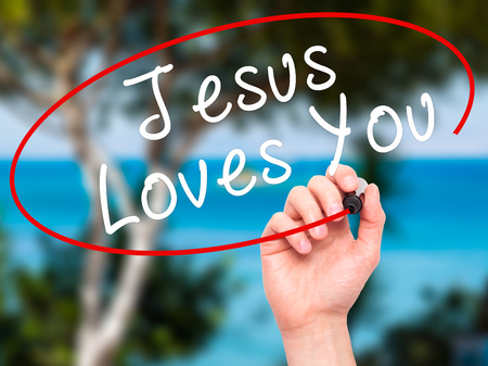 testament schreiben: Man Hand writing Jesus Loves You with black marker on visual screen. Isolated on nature. Religion, technology, internet concept. Stock Image