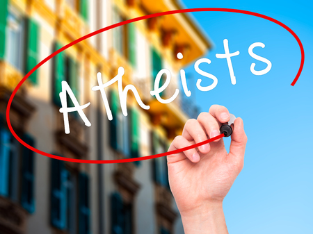 disbelieve: Man Hand writing Atheists with black marker on visual screen. Isolated on city. Business, technology, internet concept. Stock Image Stock Photo