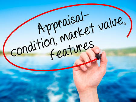 Man Hand writing Appraisal - condition, market value, features, with black marker on visual screen. Isolated on nature. Business, technology, internet concept. Stock Image Stock Photo