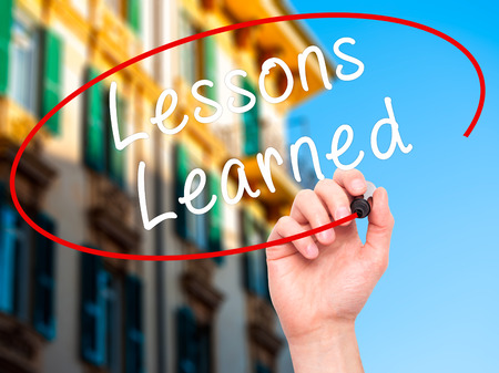 encapsulate: Man Hand writing Lessons Learned with black marker on visual screen. Isolated on city. Business, technology, internet concept. Stock Image