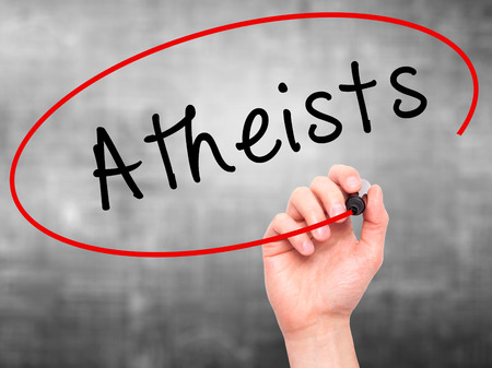 atheist: Man Hand writing Atheists with black marker on visual screen. Isolated on grey. Business, technology, internet concept. Stock Image