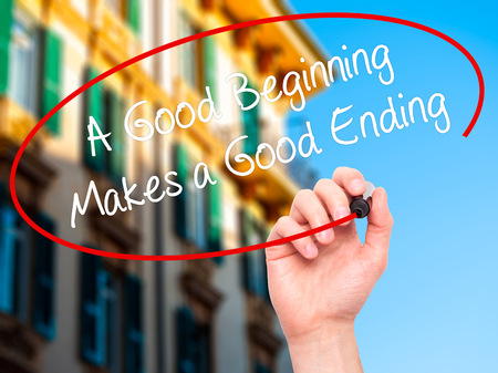 ending: Man Hand writing A Good Beginning Makes a Good Ending with black marker on visual screen. Isolated on city. Business, technology, internet concept. Stock Photo