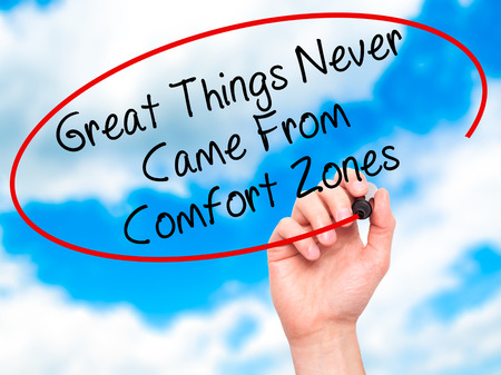 self discovery: Man Hand writing Great Things Never Came From Comfort Zones with black marker on visual screen. Isolated on sky. Business, technology, internet concept. Stock Image Stock Photo